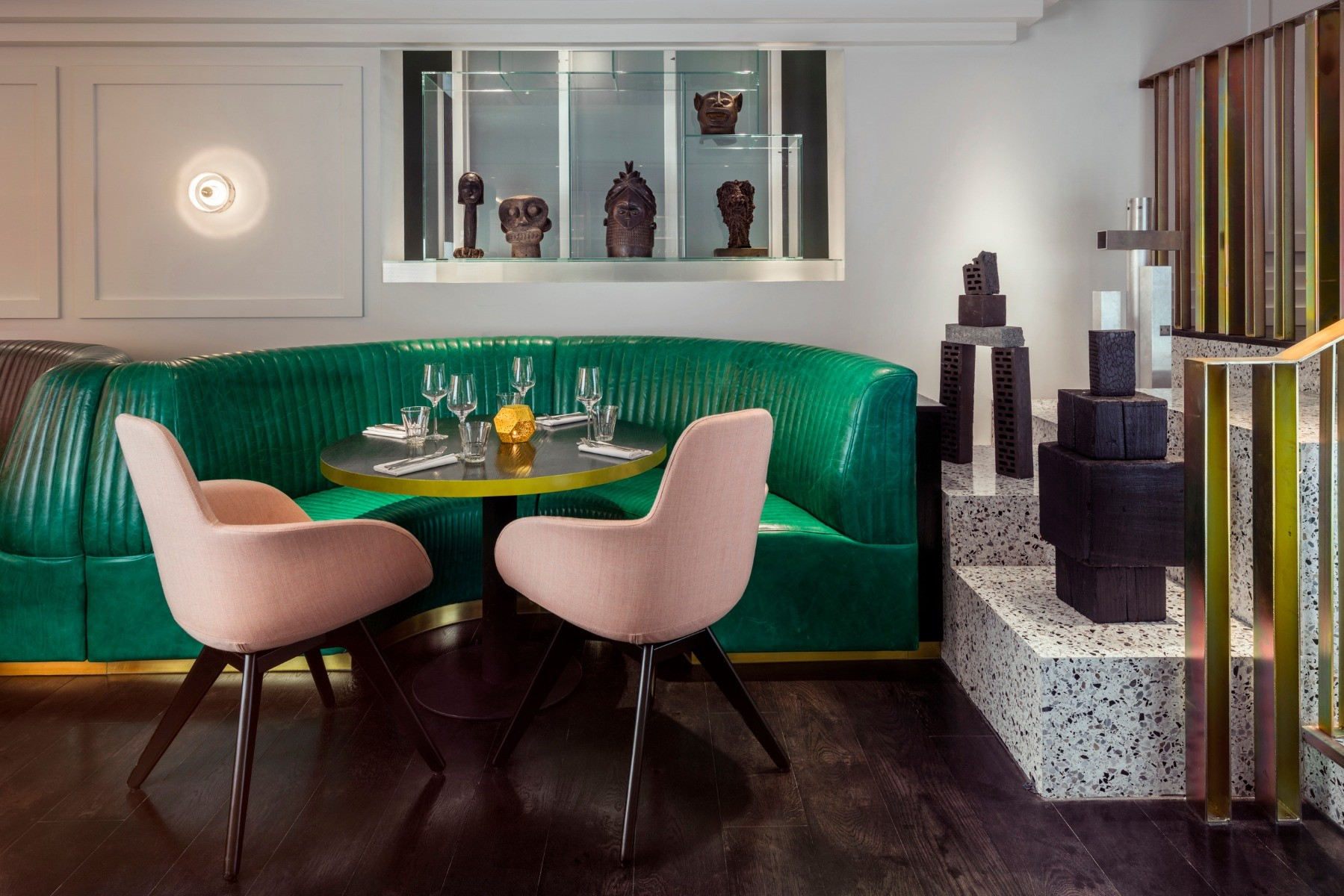 Tom Dixon Bronte Restaurant in London featuring Stone wall lights and Scoop High Back dining chairs.
