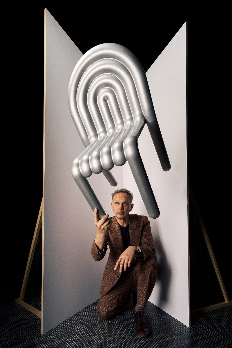 Tom Dixon holding the HYDRO Chair